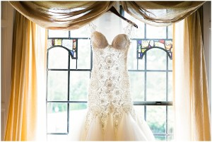 Ballgown style bridal gown featuring intricate beadwork and a large tulle skirt hangs in front of a stained glass window, Pacific Northwest wedding, Thornewood Castle wedding, wedding planning by Perfectly Posh Events, Photo by Stephanie Cristalli
