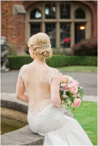 Back view of a bride sitting on the ledge of a fountain wearing a backless ballgown style wedding dress featuring intricate beadwork, Pacific Northwest wedding, Thornewood Castle wedding, wedding planning by Perfectly Posh Events, Photo by Stephanie Cristalli