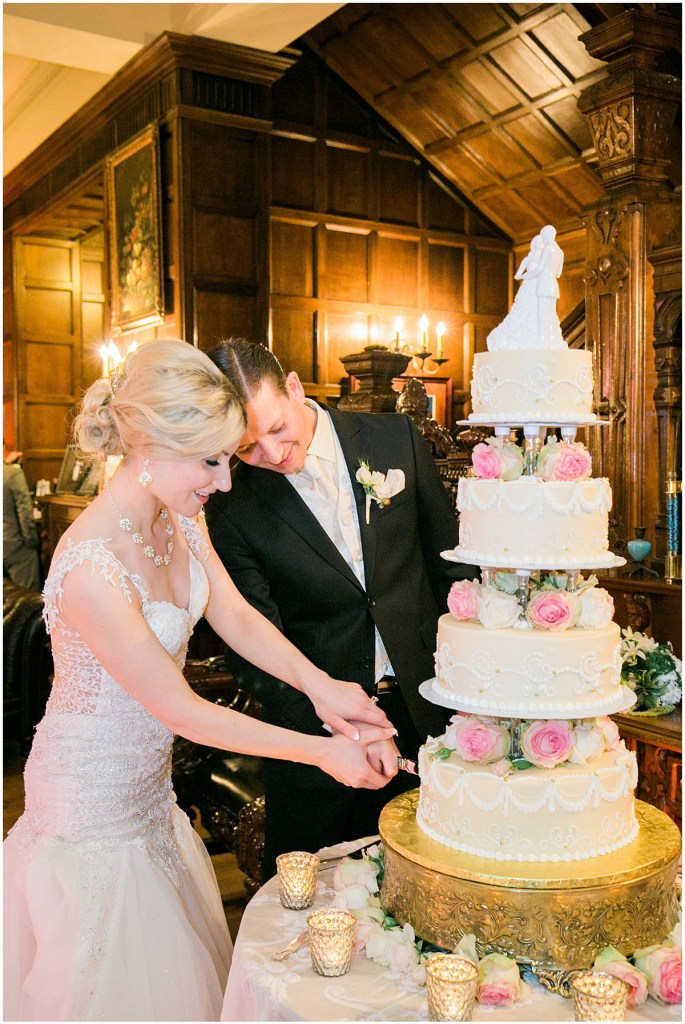 Bride and groom cut into their four tier wedding cake decorated with white frosting, pink and ivory florals, Pacific Northwest wedding, Thornewood Castle wedding, wedding planning by Perfectly Posh Events, Photo by Stephanie Cristalli