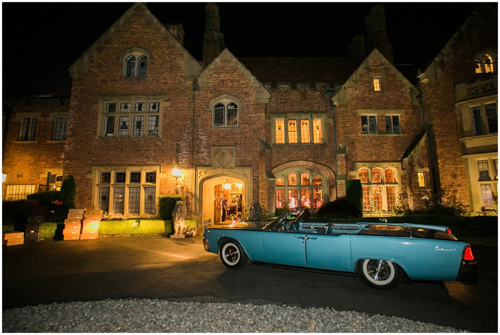 A vintage teal blue Cadillac convertible sits in front of Thornewood Castle for the bride and groom