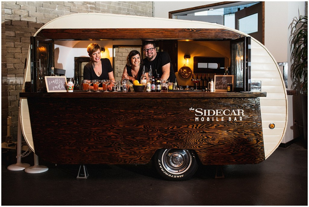 Small camper with metal and wood siding that has been reconfigured into a mobile bar is set up inside a wedding reception while bartenders create hand crafted cocktails, urban wedding, Within Sodo wedding, Seattle event planner, Perfectly Posh Events, Photo by Jenny J Photography