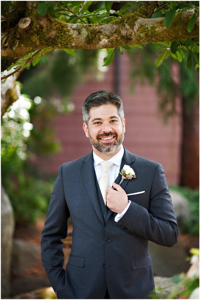 A groom in a charcoal grey suit poses outside underneath a tree, DeLille Cellars wedding, Woodinville winery, Washington wedding, Perfectly Posh Events wedding planning, Photo by Barbie Hull