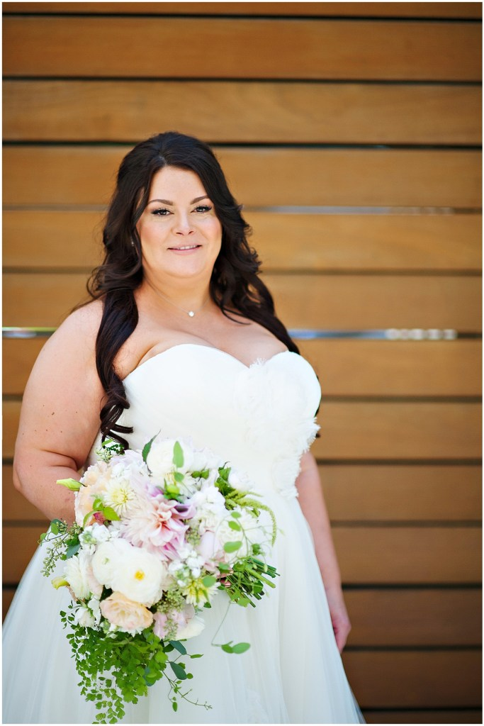 A bride in an off-white strapless wedding gown poses in front of a wood paneled wall while holding a large bouquet of pink, peach, and ivory colored flowers, DeLille Cellars wedding, Woodinville winery, Washington wedding, Perfectly Posh Events wedding planning, Photo by Barbie Hull