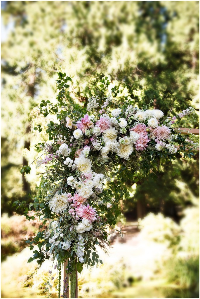 A close up of corner of a wooden arch used as a wedding altar that is covered in ivory, blush pink, and peach colored flowers and an abundance of greenery, DeLille Cellars wedding, Woodinville winery, Washington wedding, Perfectly Posh Events wedding planning, Photo by Barbie Hull