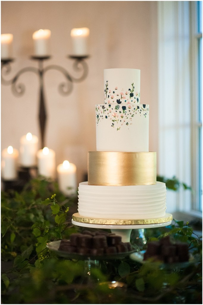 Four tier wedding cake covered in white frosting and one tier covered in gold frosting with small pink and navy flowers with leaves painted onto the top layers, DeLille Cellars wedding, Woodinville winery, Washington wedding, Perfectly Posh Events wedding planning, Photo by Barbie Hull