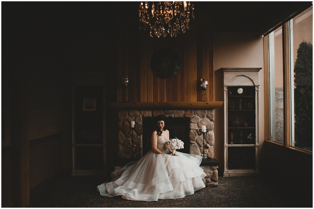 Bride holds a large white floral bouquet while sitting in front of a rustic stone fireplace, Edgewater Hotel, Seattle wedding, Washington wedding coordinator, Perfectly Posh Events, Photo by Carina Skrobecki