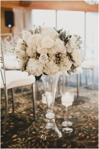 A large vase lining a wedding ceremony aisle filled with a bouquet of white and ivory flowers circled by three candles, Edgewater Hotel, Seattle wedding, Washington wedding coordinator, Perfectly Posh Events, Photo by Carina Skrobecki