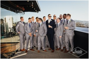Groom in a dark navy suit hangs out with his groomsmen in grey tuxedo on a rooftop deck while drinking Rainier beer, Fremont Foundry, Seattle wedding, Perfectly Posh Events wedding planning, Photo by Laurel McConnell Photography