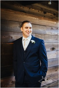 Groom in a dark navy suit a gold tie poses in front of a rustic wood wall, Fremont Foundry, Seattle wedding, Perfectly Posh Events wedding planning, Photo by Laurel McConnell Photography