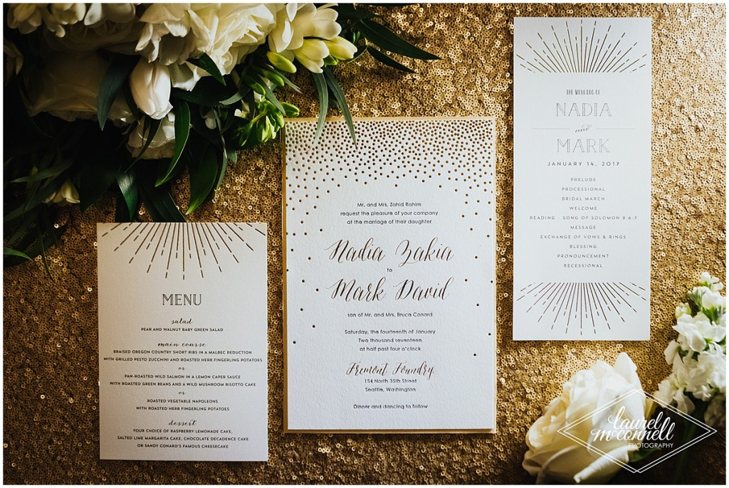 Custom designed wedding invitations with gold lettering on off-white paper sit atop a gold sequined table cloth, Fremont Foundry, Seattle wedding, Perfectly Posh Events wedding planning, Photo by Laurel McConnell Photography
