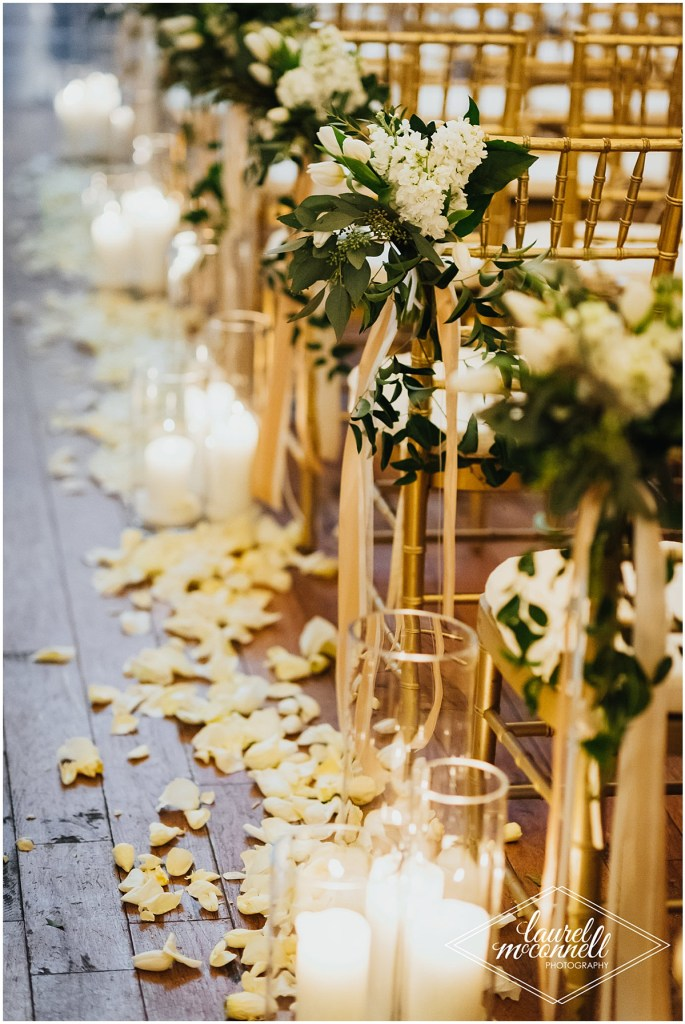 Close up of gold chairs set up for an indoor wedding ceremony decorated with ivory flowers and greenery with large white pillar candles and white rose petals framing the aisle, Fremont Foundry, Seattle wedding, Perfectly Posh Events wedding planning, Photo by Laurel McConnell Photography
