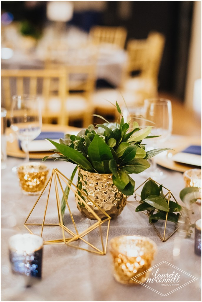 Wedding dinner table centerpiece with greenery in a small gold vase, gold geometric shapes, and votive candles on a light grey table cloth, Fremont Foundry, Seattle wedding, Perfectly Posh Events wedding planning, Photo by Laurel McConnell Photography