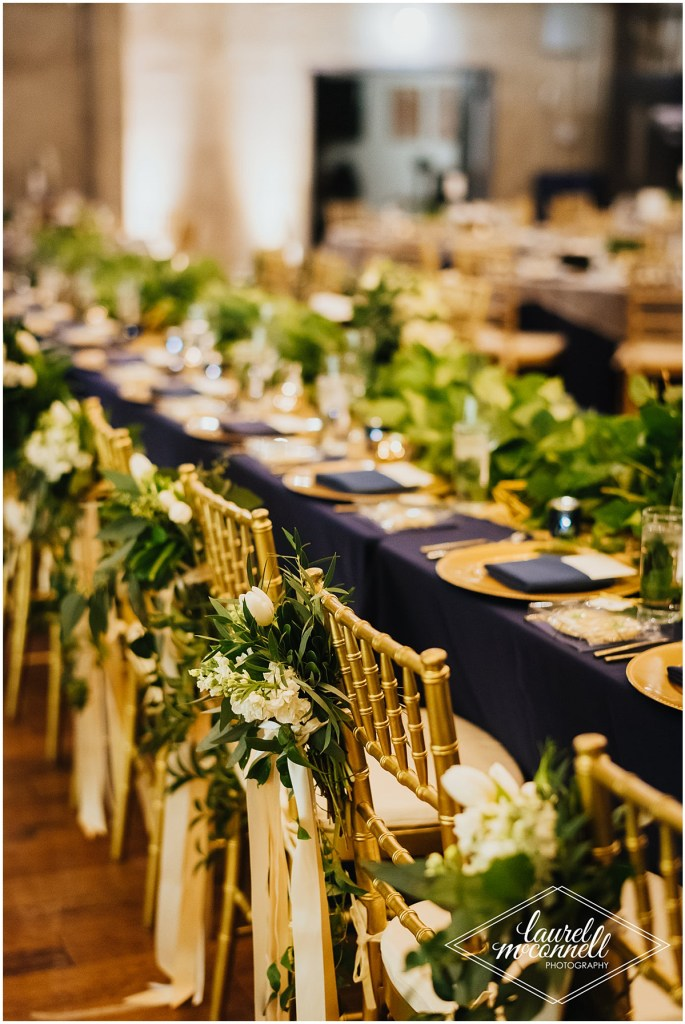 Long wedding reception dinner table covered in a navy table cloth and decorated with gold chargers and an abundance of greenery with gold chairs that are also decorated with ivory flowers and greenery, Fremont Foundry, Seattle wedding, Perfectly Posh Events wedding planning, Photo by Laurel McConnell Photography