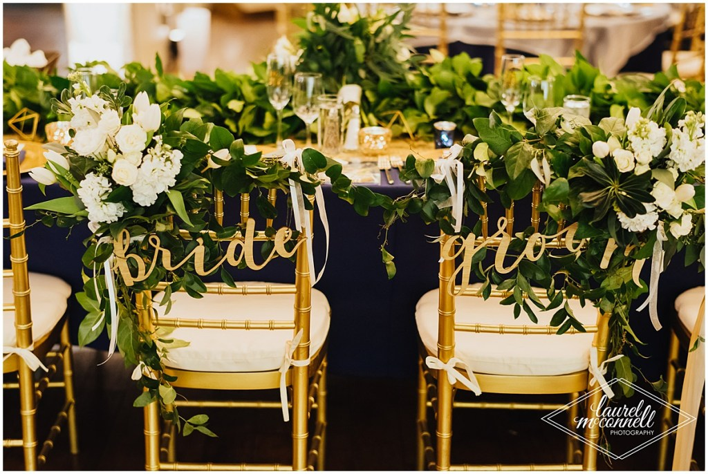 Gold chairs draped with white flowers and greenery and gold glitter bride and groom signs sit in front of a wedding reception dinner table decorated with an overflow of greenery, Fremont Foundry, Seattle wedding, Perfectly Posh Events wedding planning, Photo by Laurel McConnell Photography