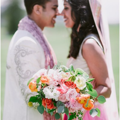 A bride and groom pose outside while the bride holds a large bouquet with ivory, blush pink, and orange flowers, Dairyland wedding, Snohomish county wedding, Hindu wedding, wedding planning by Perfectly Posh Events, Photo by Barrie Anne Photography