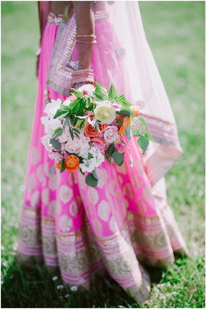 A view of a Hindu bride's traditional patterned pink wedding gown with an ivory, blush pink, and orange floral bouquet, Dairyland wedding, Snohomish county wedding, Hindu wedding, wedding planning by Perfectly Posh Events, Photo by Barrie Anne Photography