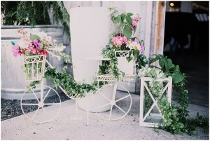 White caste iron decorative bike and plant stands overflowing with violet, magenta, and ivory colored florals with greenery, Dairyland wedding, Snohomish county wedding, Hindu wedding, wedding planning by Perfectly Posh Events, Photo by Barrie Anne Photography