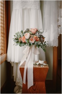 A bride's dress and veil hangs from the wall and the bridal bouquet made of ivory and peach flowers with succulents and greenery sealed with a blush colored ribbon, DeLille Cellars winery, Woodinville Washington wedding, event planning by Perfectly Posh Events , Photo by Kristen Marie Parker
