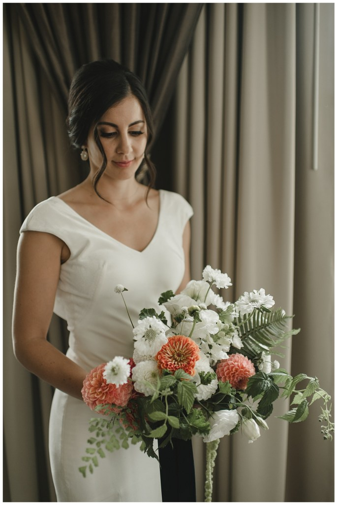 Bride in white velvet wedding dress at Axis Pioneer Square in Seattle with wedding bouquet featuring white flowers, pops of orange flowers, greenery, wild textures and ferns | Wedding Planning + Design by Perfectly Posh Events | Photo by CARINA SKROBECKI | #perfectlyposhevent