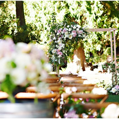 Garden ceremony with lush flowers and large ceremony arch with asymmetrical flowers and greenery | Whimsical and Romantic Wedding at DeLille Cellars | Wedding Planning & Design by Perfectly Posh Events | Wedding Photos by Barbie Hull Photography | Wedding Flowers by Floressence | #perfectlyposhevents