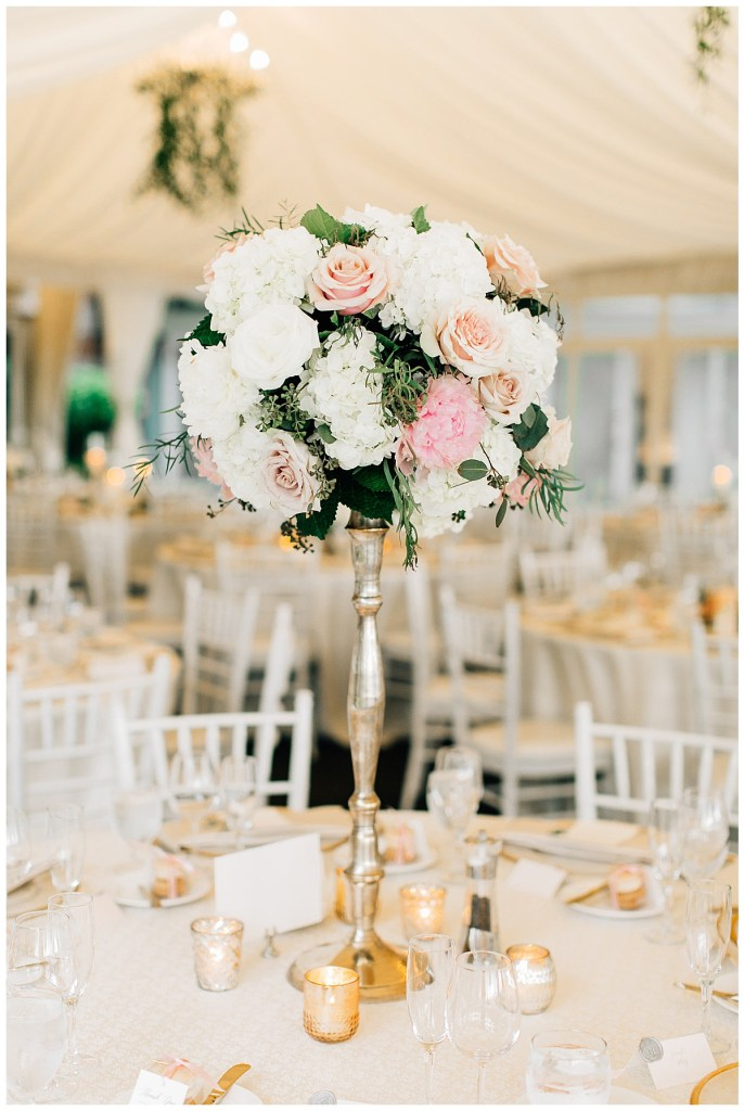 Tall, white and blush floral centerpiece with greenery on guest dinner tables in a white tent. Click for more classic wedding inspiration from this waterfront wedding in Seattle at the Woodmark Hotel wedding venue.  Event planning by Perfectly Posh Events, based in Seattle and Portland.  Wedding photography by Jenna Bechtholt Photography.  Wedding flowers by Flora Nova Design. Linens by BBJ Linen. #perfectlyposhevents