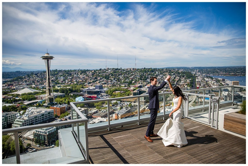 Hetal + Jake share a tender moment after their first look overlooking Seattle as Jake twirls Hetal in her wedding dress.