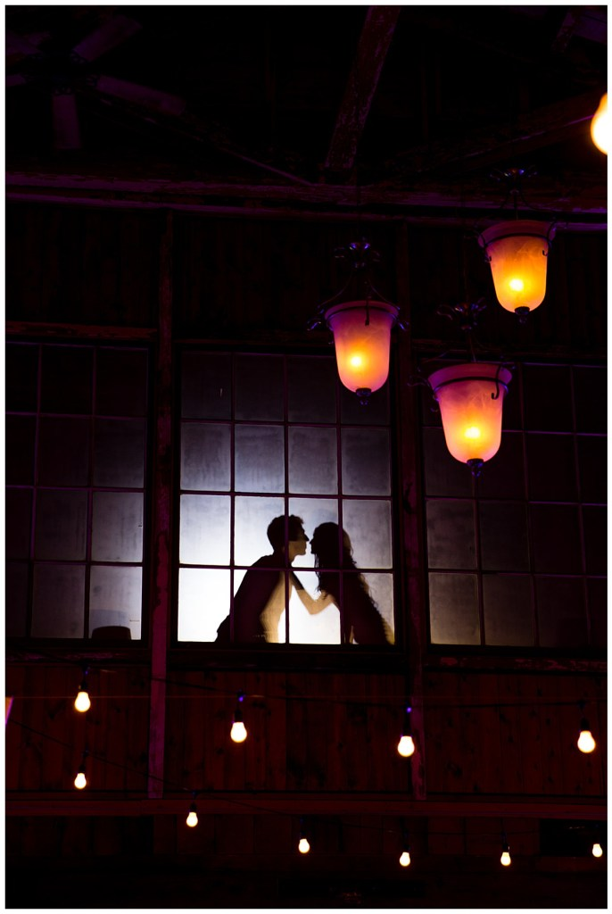 Hetal + Jake are seen kissing behind the window while their guests enjoy the night below.