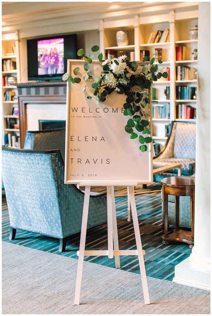 Elena + Travis's welcome sign greeted guests with a modern typography and a romantic floral swag.