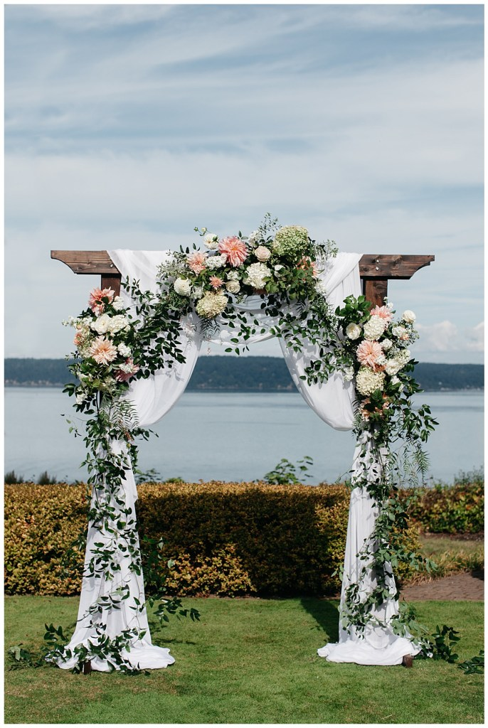 Wood wedding reception arch with romantic wedding flowers and white draping.