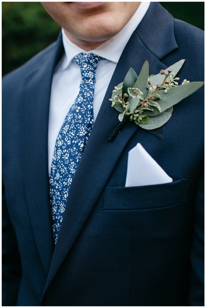 Simple groom's boutonniere with navy suit and navy pattern tie.