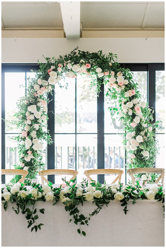 Arch with blush and white roses and greenery for head table at wedding reception.