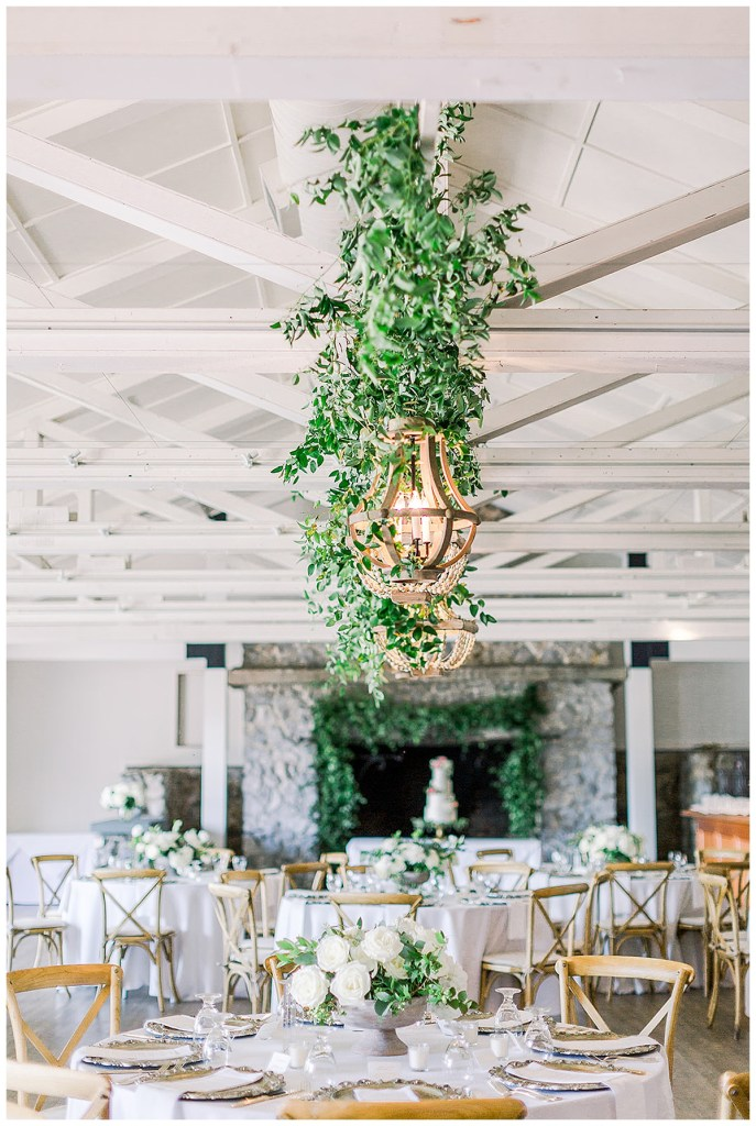 Greenery wrapped around chandeliers for wedding reception.