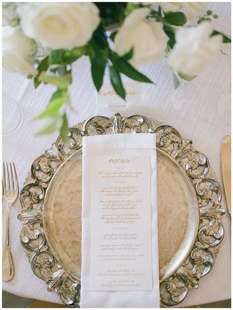 Silver charger and wedding reception menu with white napkin.