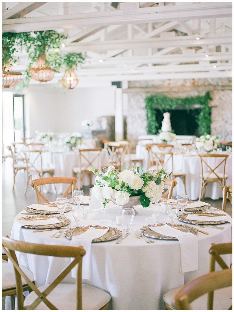 Classic and clean white wedding reception centerpieces and greenery.