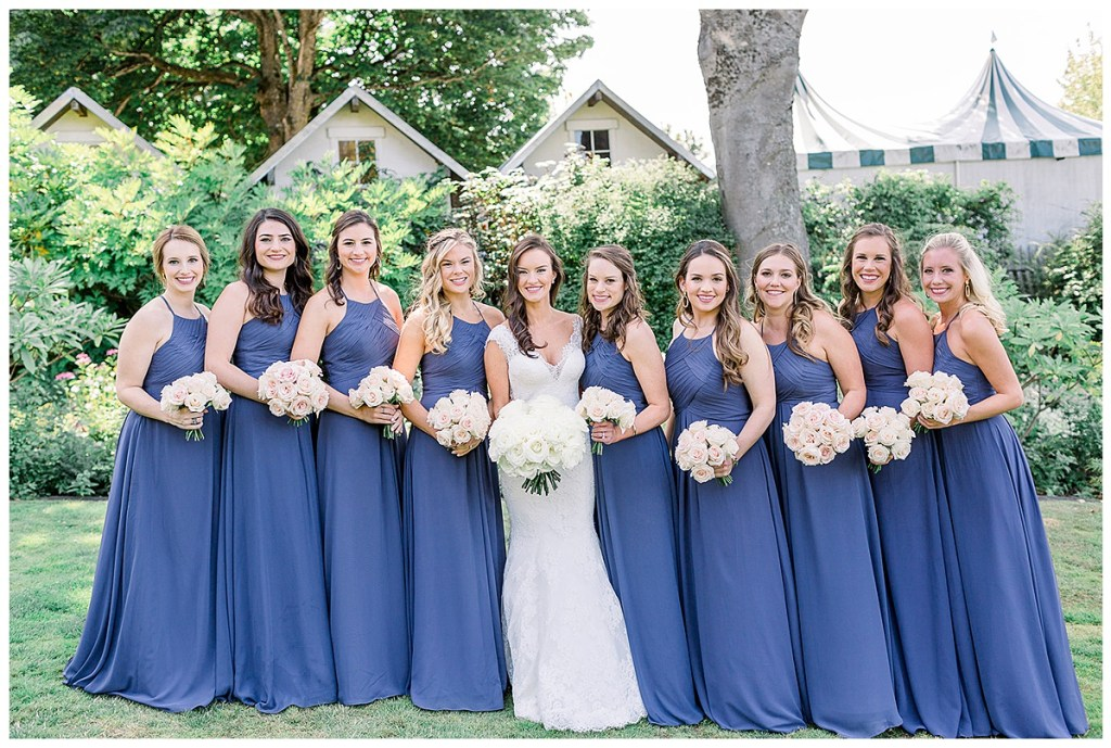 All blue bridesmaids dresses with simple blush bouquets.