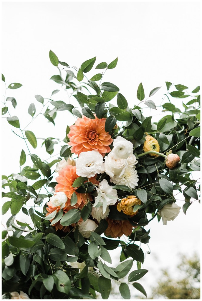 Orange and yellow and white wedding flowers with greenery.