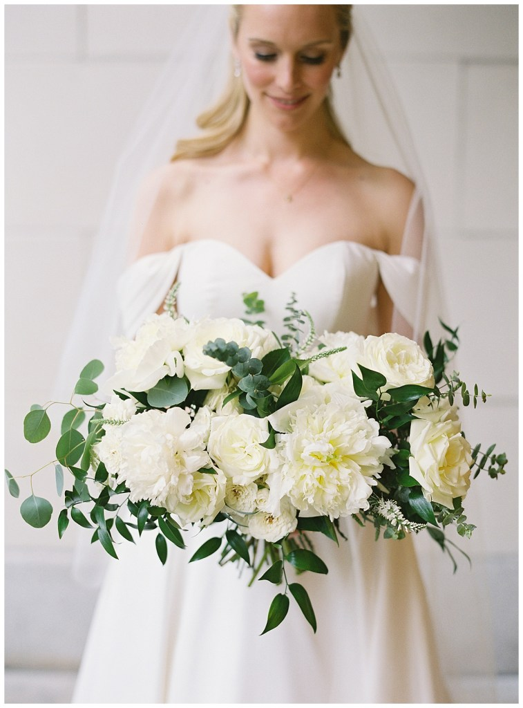 White with greenery bridal bouquet and off the shoulder white wedding dress.