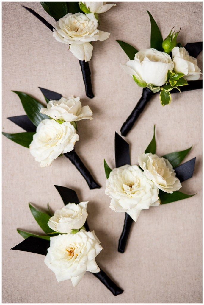 Simple white flower boutonniere with greenery and navy blue satin wrap ribbon.