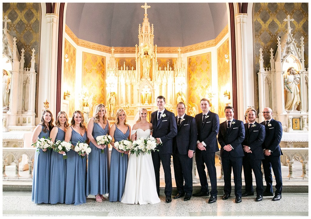 All navy groomsmen suits and blue bridesmaids dresses with white bouquets and greenery in Seattle, WA.