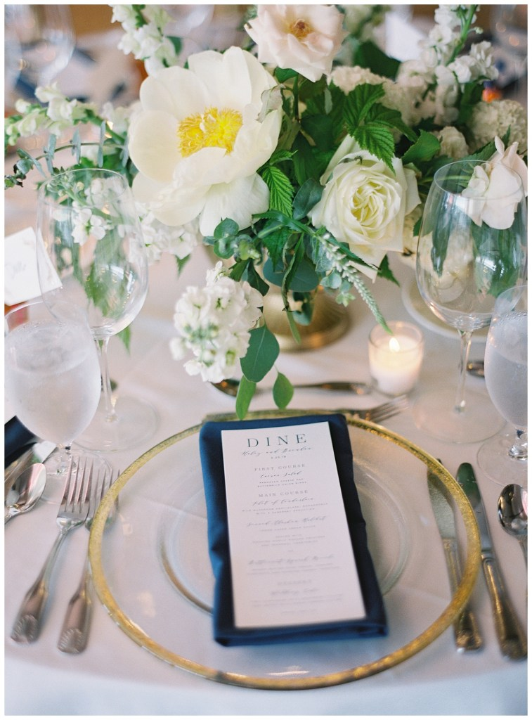 Gold rim charger and navy napkin with wedding reception menu place setting.