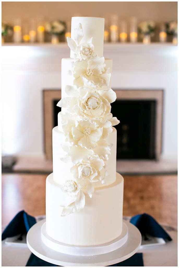A five-tier monochromatic white wedding cake with couture-style floral detail.