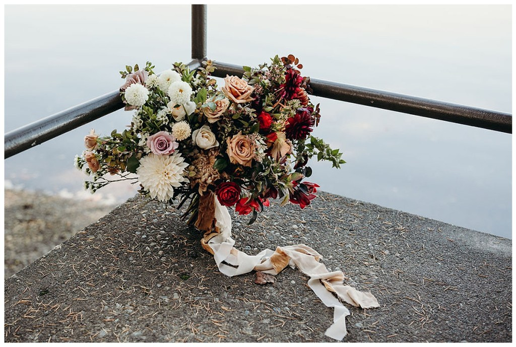 Boho bridal bouquet with jewel toned florals and greenery with a wild and loose feel and trailing ribbon in wedding at Alderbrook Resort & Spa, WA.