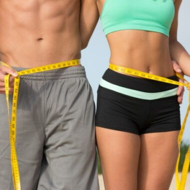 fit couple measuring waist as weight loss concept