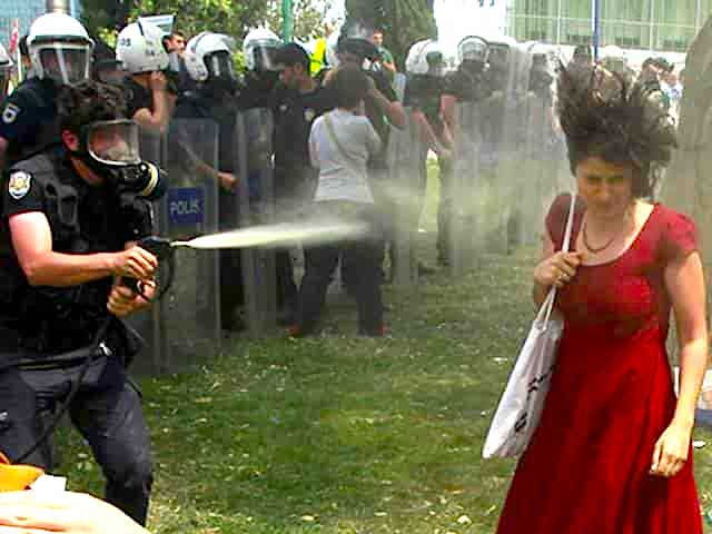 woman in red dress being tear-gassed