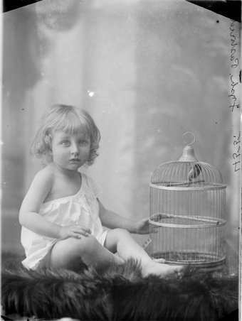Small child with caged bird, sitting on rug with legs crossed, whole-length, full face, ca. 1880-ca. 1900. (www.slv.vic.gov.au)