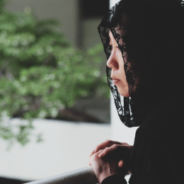 Lady in black silk head scarf looking over balcony with trees in background. Image for Hawa.