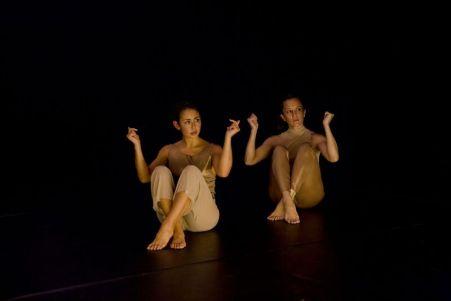 Melanie Lane and Lillian Steiner in beige costumes sitting on stage