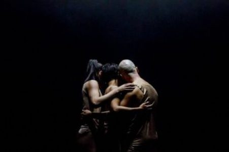three people on a dark stage facing away from the camera. Night Dance production. Credit: Arts House