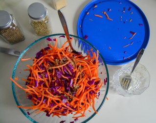 mixing carrot salad by shaking the bowl