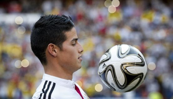 New Real Madrid player James Rodriguez from Colombia plays with a ball and poses for photographers, during his official presentation at the Santiago Bernabeu stadium in Madrid, Spain, Tuesday, July 22, 2014, after signing for Real Madrid. Real Madrid have signed Rodriguez from Monaco on a six-year contract,  (AP Photo/Daniel Ochoa de Olza)